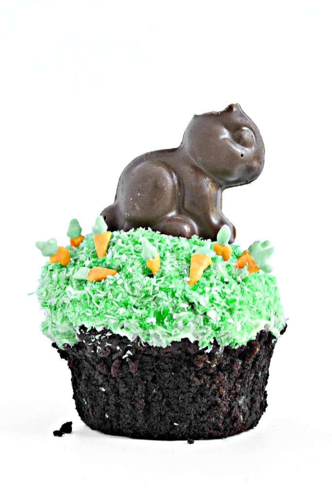 "A gluten free cupcake, topped with all-natural coconut ""grass,"" scattered with carrot sprinkles and topped with the cutest vegan almond butter-filled chocolate bunny."