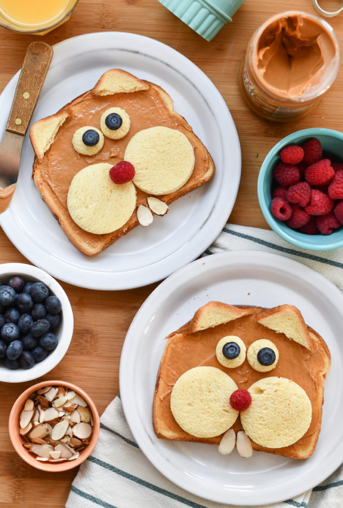 Two plates with toast made to look like groundhogs on a table with fruit in a bowl.