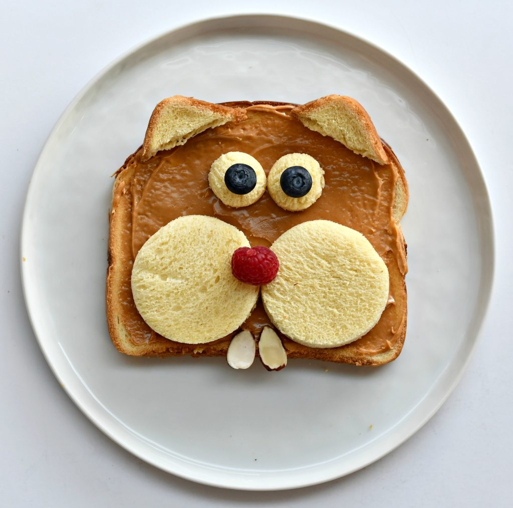 A piece of bread on a plate that looks like a groundhog.