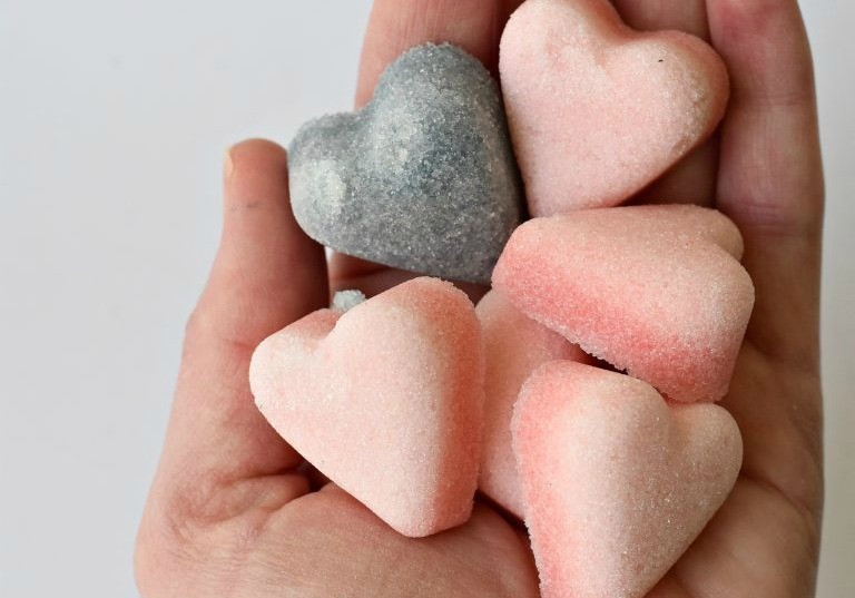 A hand holding heart-shaped sugar cubes colored pink and purple