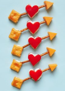 A white background of 5 edible Cupid arrows made with bell peppers, cheese, pretzels, and Cheez-its crackers.